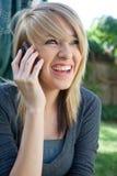 Adolescente felice di risata sul telefono mobile delle cellule Fotografia Stock Libera da Diritti