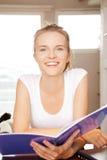 Adolescente felice e sorridente con il grande blocco note Fotografie Stock