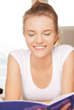 Adolescente felice e sorridente con il grande blocco note Immagine Stock Libera da Diritti