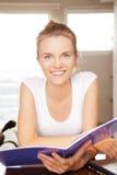 Adolescente felice e sorridente con il grande blocco note Immagine Stock