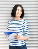 Adolescente felice e sorridente con il grande blocco note Fotografie Stock Libere da Diritti