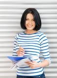 Adolescente felice e sorridente con il grande blocco note Fotografia Stock
