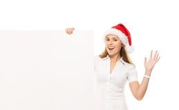 Adolescente felice in un cappello di Natale che tiene una grande insegna Immagini Stock Libere da Diritti