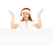 Adolescente felice in un cappello di Natale che tiene una grande insegna Fotografia Stock