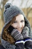 Adolescente feliz al aire libre que lleva el sombrero y mittnes blancos y negros del invierno Imagenes de archivo