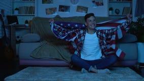 Adolescente feliz com bandeira americana que cheering a casa favorita da equipe de esportes, emoções vídeos de arquivo