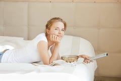 Adolescente feliz com telecontrole e pipoca da tevê Imagem de Stock