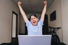 Adolescente feliz con alegría aumentó sus manos que se incorporaban en el ordenador en el cuarto de la casa Fotos de archivo libres de regalías