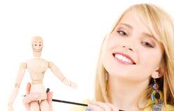 Adolescente feliz con el maniquí modelo de madera Fotos de archivo