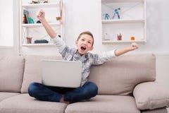 Adolescente feliz con el ordenador portátil en casa Fotos de archivo libres de regalías