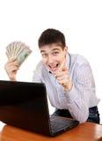 Adolescente feliz con el ordenador portátil y el dinero Imagenes de archivo