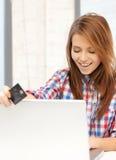 Adolescente feliz con el ordenador portátil y la tarjeta de crédito Foto de archivo