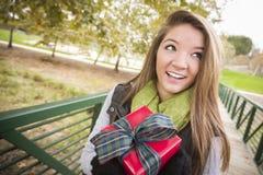Adolescente feliz con el regalo envuelto con el arco afuera Fotos de archivo