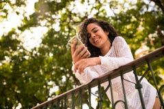 Adolescente feliz con el teléfono móvil a disposición Imagen de archivo