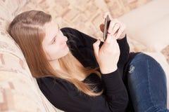Adolescente feliz con el teléfono móvil que se sienta en el sofá en la sala de estar Fotos de archivo libres de regalías