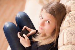 Adolescente feliz con el teléfono móvil que se sienta en el sofá en la sala de estar Fotos de archivo