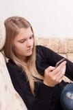 Adolescente feliz con el teléfono móvil que se sienta en el sofá en la sala de estar Imagenes de archivo