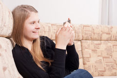 Adolescente feliz con el teléfono móvil que se sienta en el sofá en la sala de estar Imágenes de archivo libres de regalías