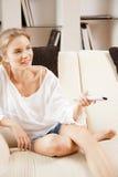 Adolescente feliz con el telecontrol de la TV Fotos de archivo