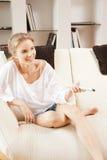 Adolescente feliz con el telecontrol de la TV Foto de archivo libre de regalías