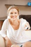 Adolescente feliz con el telecontrol de la TV Imagen de archivo