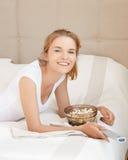 Adolescente feliz con el telecontrol y palomitas de la TV Imagen de archivo