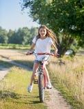 Adolescente feliz con la bicicleta larga del montar a caballo del pelo en campo en el día soleado Fotos de archivo libres de regalías