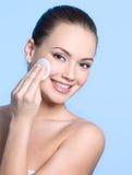 Adolescente feliz con la cara de la limpieza de la esponja de algodón Imágenes de archivo libres de regalías