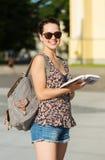 Adolescente feliz con la guía turística y la mochila Foto de archivo libre de regalías