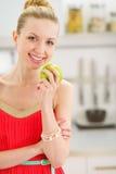 Adolescente feliz con la manzana en cocina Imagen de archivo libre de regalías