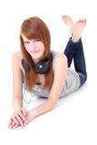 Adolescente feliz con la mentira de los auriculares Imagenes de archivo
