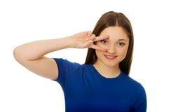 Adolescente feliz con la muestra de la victoria en ojo Foto de archivo libre de regalías