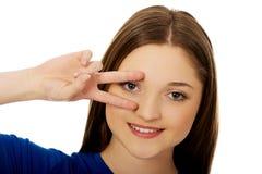 Adolescente feliz con la muestra de la victoria en ojo Fotos de archivo
