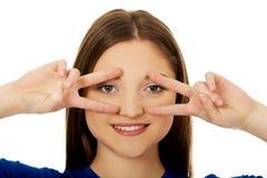 Adolescente feliz con la muestra de la victoria en ojos Imagen de archivo libre de regalías