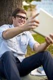 Adolescente feliz con la PC de la tableta que toma el selfie Fotos de archivo