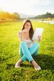 Adolescente feliz con la tableta en naturaleza Imagen de archivo