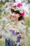 Adolescente feliz con las flores en la cabeza en jardín Fotografía de archivo