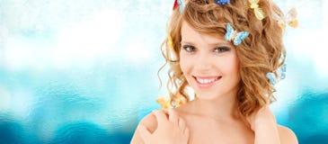 Adolescente feliz con las mariposas en pelo Imágenes de archivo libres de regalías