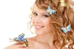 Adolescente feliz con las mariposas en pelo Imagenes de archivo
