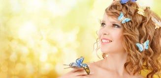 Adolescente feliz con las mariposas en pelo Foto de archivo libre de regalías
