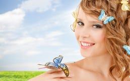 Adolescente feliz con las mariposas en pelo Imagen de archivo libre de regalías