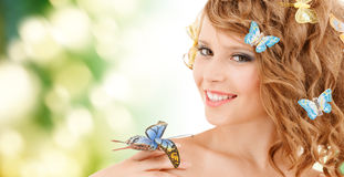 Adolescente feliz con las mariposas en pelo Fotografía de archivo libre de regalías