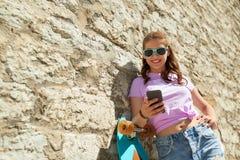 Adolescente feliz con longboard y smartphone Imagenes de archivo