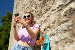 Adolescente feliz con longboard y smartphone Imagen de archivo libre de regalías