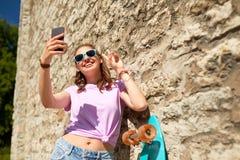 Adolescente feliz con longboard y smartphone Fotos de archivo libres de regalías
