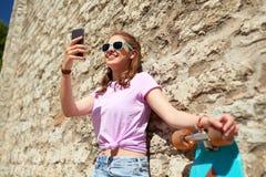 Adolescente feliz con longboard y smartphone Imágenes de archivo libres de regalías