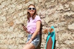 Adolescente feliz con longboard y smartphone Fotos de archivo