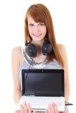 Adolescente feliz con los auriculares y la computadora portátil Fotos de archivo