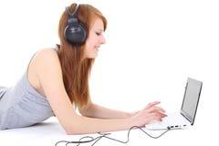 Adolescente feliz con los auriculares y la computadora portátil Imagen de archivo
