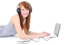 Adolescente feliz con los auriculares y la computadora portátil Fotografía de archivo